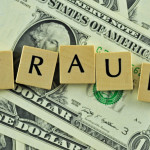 Word fraud in letters on background of dollar banknotes
