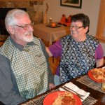 senior couple eating dinner, wearing tidy top apron