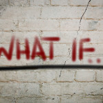 "Red ""what if?"" words painted on gray brick wall"