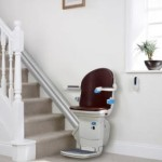 Photo of a stairlift in place at the bottom of the stairs.
