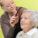 senior woman with her caregiver who is combing her hair