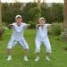 2 seniors exercising on the grass near palm trees
