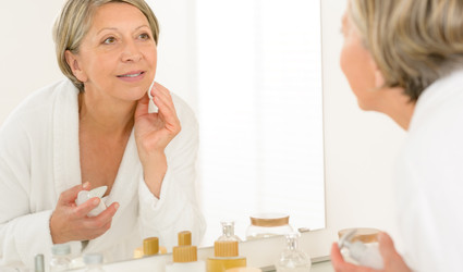 Pretty senior woman in bathroom looking at herself in mirror while applying moisturizing lotion