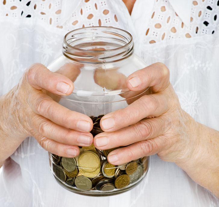 a senior woman holding a jar of coins