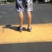 man standing on a yellow painted speed bump