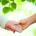 Holding hands with senior over green leaves background