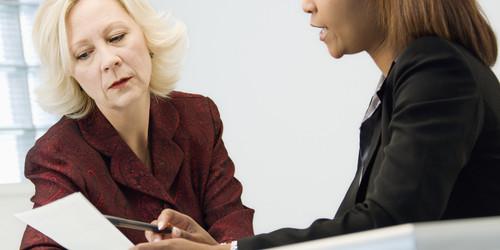 Businesswomen sitting at office desk discussing paperwork.