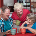 Group of laughing seniors in a coffeehouse