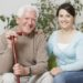Smiling senior man holding cane and sitting with grandaughter