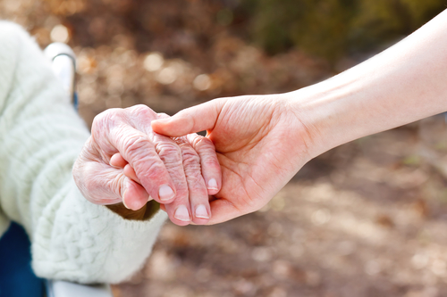 Senior Lady Holding Hands with Younger Caregiver