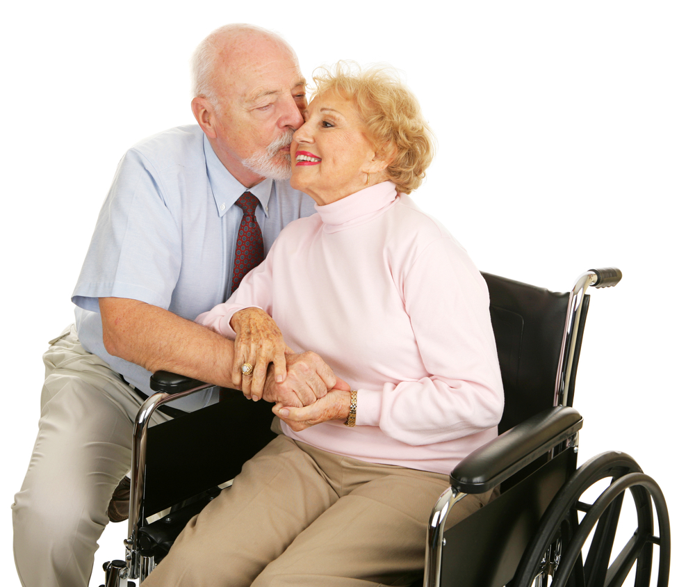 Affectionate senior husband giving his disabled wife a kiss on the cheek. Isolated on white.