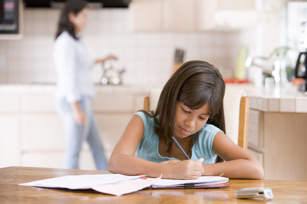 Young girl in kitchen doing homework with woman in background