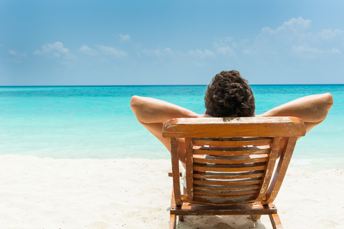 person resting in a beach chair by the shore