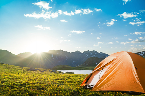 tourist tent camping in mountains by a lake during daylight